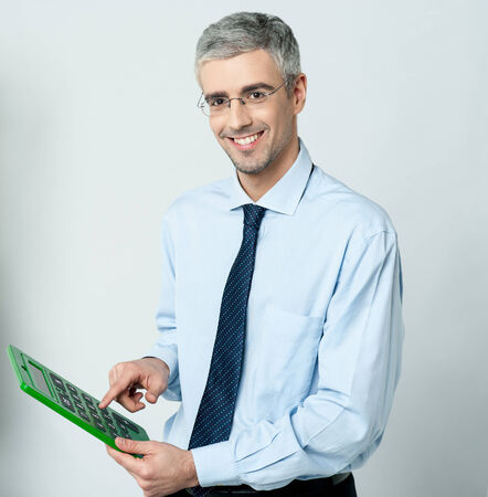 Smiling corporate man working in big green calculator photo