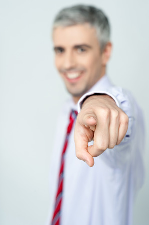Young businessman pointing finger at viewer