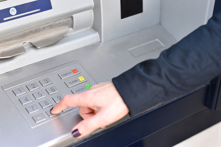 Woman hand entering code into atm machine photo