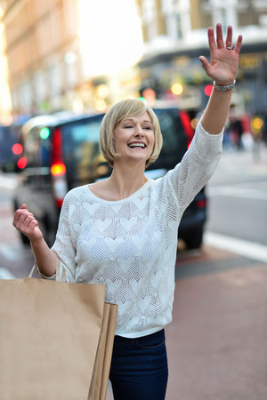 hailing: Woman with shopping bags hailing a taxicab in the street