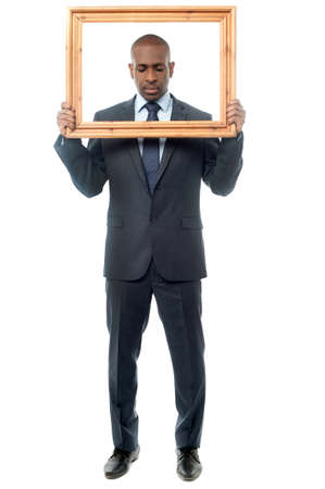 Middle aged man standing behind wooden picture frame