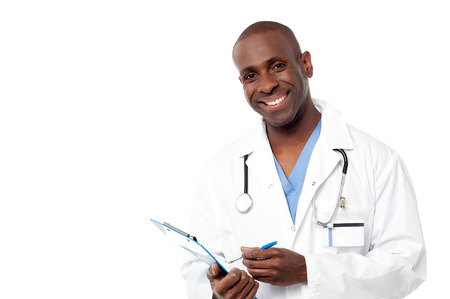 Smiling male physician writing prescription photo