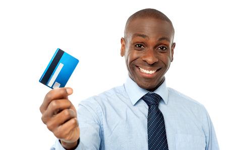 držení: Usmívající se firemní muž ukazuje svou debetní kartu Reklamní fotografie