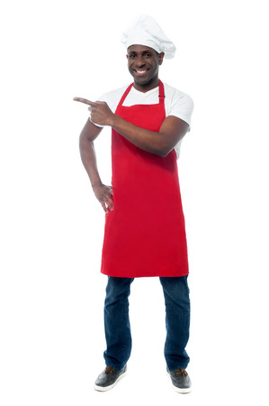 caterer: Full length portrait of chef in uniform pointing away