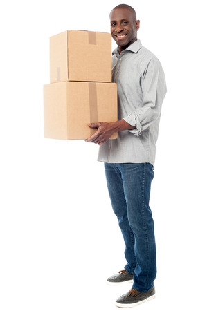 Handsome male with with stack of boxes isolated on white photo