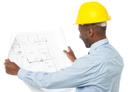 man rear view: Construction engineer with hardhat reviewing building plan Stock Photo