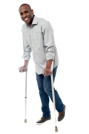 Smiling man with crutches trying to walk photo