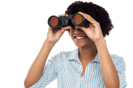 Beautiful smiling woman looking through binocular photo