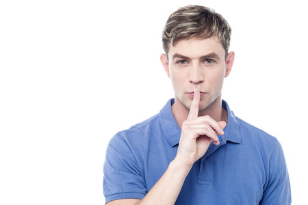 Handsome young man making a silence gesture