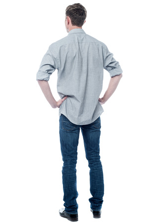 man rear view: Back pose, full length shot of a young man looks ahead Stock Photo