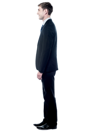 businessman standing: Side view of businessman standing isolated on white