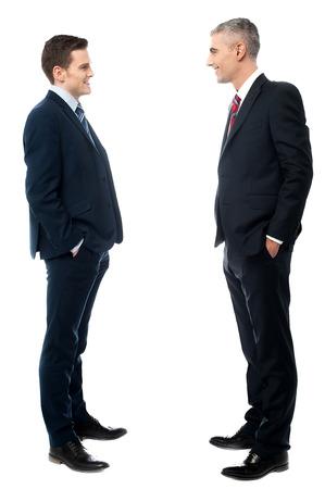 Geschäftsleute Gespräch zusammen, die Hände in den Taschen