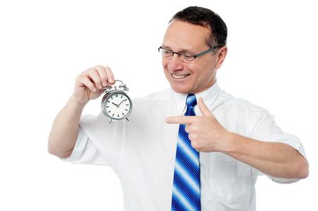 Smiling businessman holding an alarm clock Stock Photo