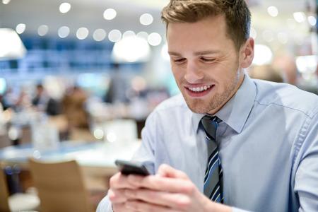 携帯電話を使用してのカフェで笑顔の実業家 写真素材