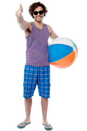 Young man with beach ball and showing thumbs up