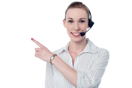 Happy customer support executive in headset pointing away photo
