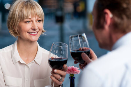 Mid aged couple toasting with glasses of wine photo