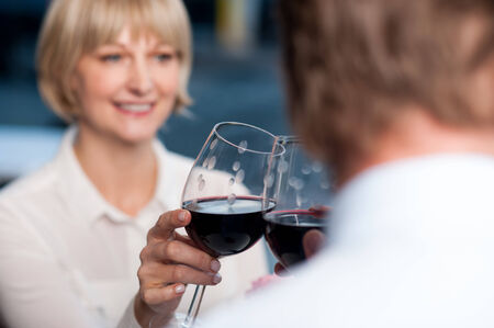 raises: Attractive couple raises a glass of red wine in cafe