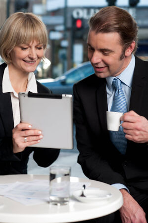 Corporate people discussing business with tablet computer photo