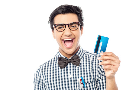 Young cheerful man showing his credit card to camera photo
