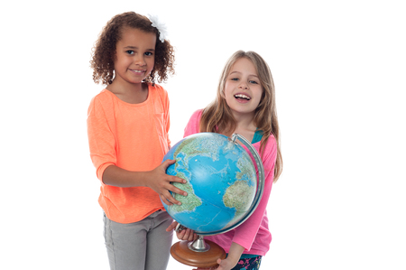 School girls locating countries on globe photo