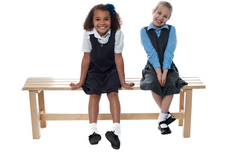 uniform skirt: Two cute girls laughing sitting on a bench Stock Photo