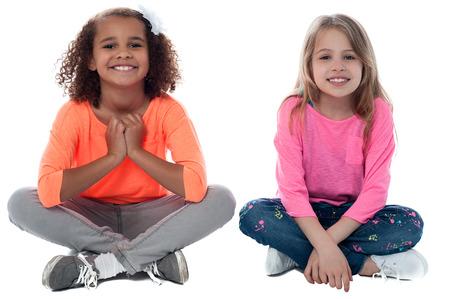 Hübsche Mädchen, die auf dem Boden sitzen und spielen