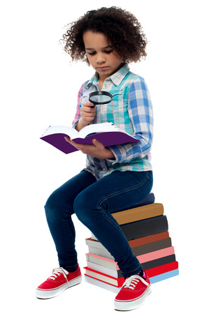 School girl sitting on the heap of books and reading photo