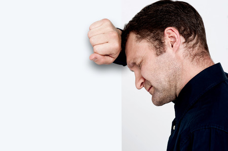 Side view of depressed man leaning his head against a wall