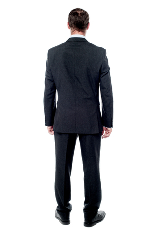 Rear view of businessman posing a wall