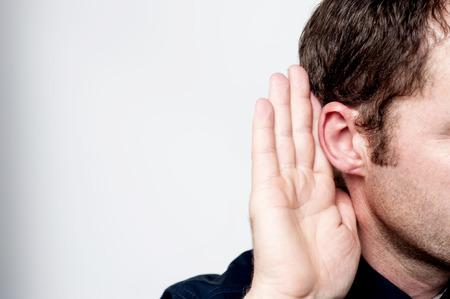 escuchar: Escuchando hombre sostiene su mano cerca de la oreja