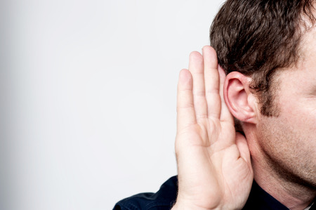hearsay: Listening male holds his hand near his ear