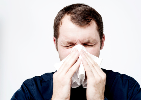Man blowing his nose in a tissue photo