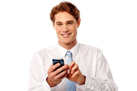 operate: Handsome young executive texting with smartphone Stock Photo