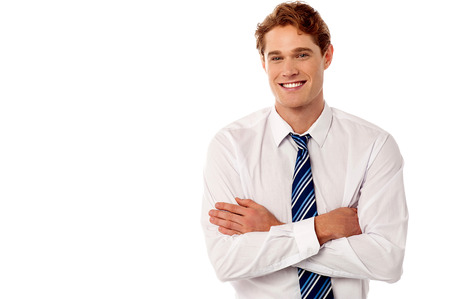 Smiling young male executive with folded arms photo