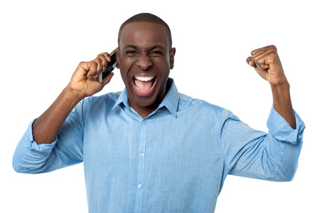 excited man: Happy man with cell phone, clenching fists in excitement Stock Photo