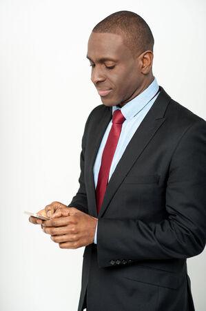 Smiling businessman sending message using mobile phone photo