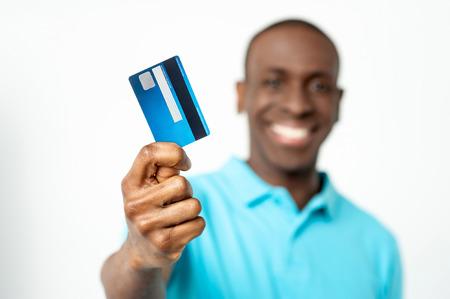 ハンサムな男がカメラに彼のデビット カードを表示