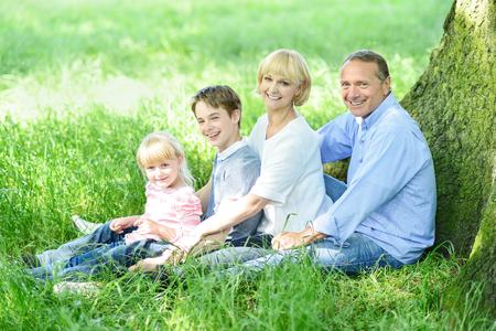 jovial: Jovial family resting under a tree in shade