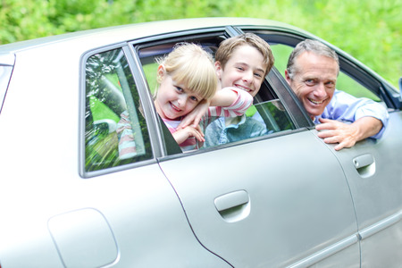man looking out: Father enjoying car drive with his kids Stock Photo