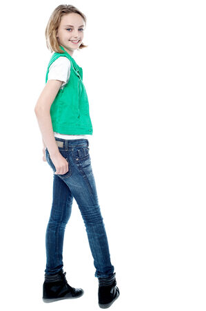 Smiling young girl turning back, hands in pocket photo