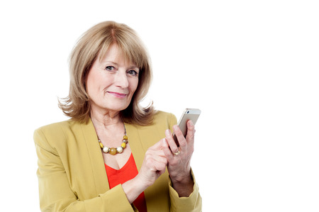 Mature woman dialing on a phone in a studio photo