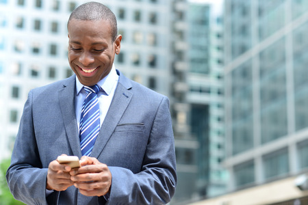 Handsome african businessman reading email on smart phone photo