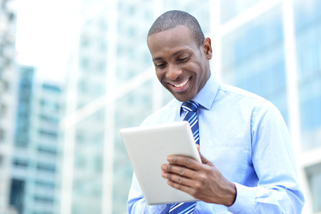 Businessman in formals using tablet device photo
