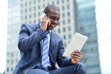 휴대 전화를 얘기하는 동안 사업가 태블릿을 찾고