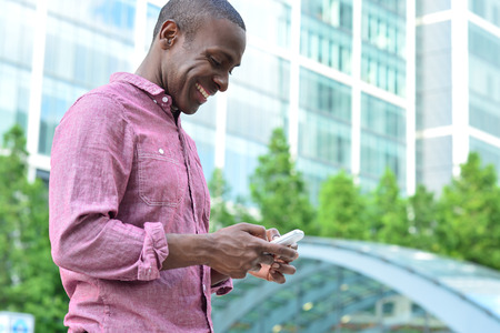 Handsome african man texting to his friend photo