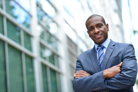 empresario: Hombre de negocios confidente que presenta cerca de su edificio de oficinas