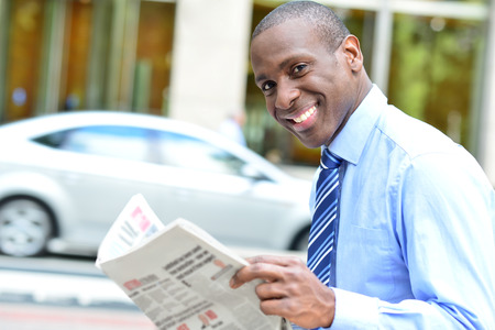 chronicle: Corporate man reading daily chronicle and smiling to camera