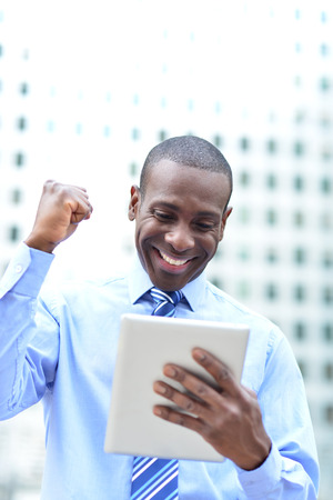 Successful businessman clenching fists with digital tablet photo