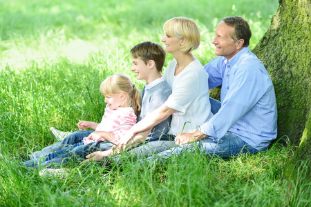 Family of four sitting in row under tree photo